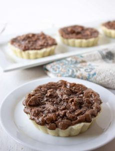 Mini Chocolate Walnut Tarts filled with chopped walnuts.