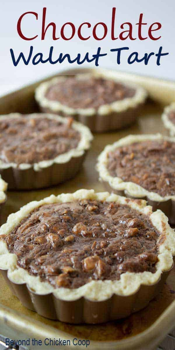 Mini Chocolate Walnut Tarts on a baking tray.