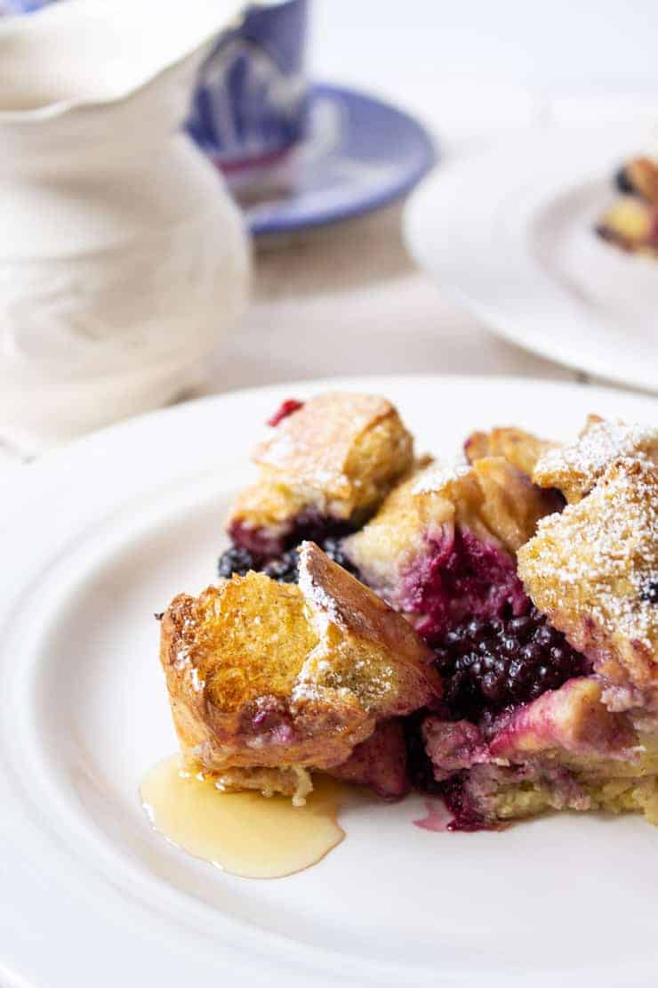 French Toast Casserole with blackberries and topped with maple syrup.