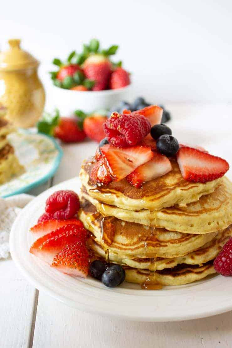 Four pancakes stacked and topped with fresh strawberries, raspberries and blueberries.