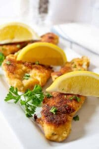 Pan Fried Walleye served with fresh lemons and topped with chopped parsley.