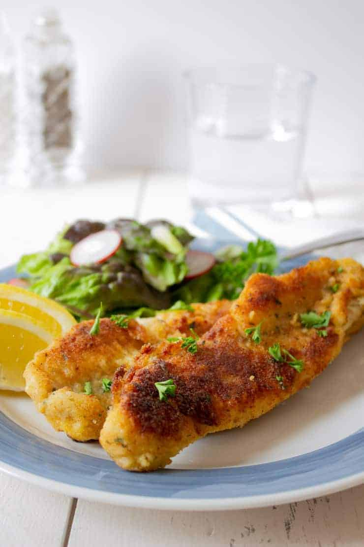 Pan Fried Walleye on a plate with lemons and a salad.