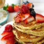 A stack of quinoa pancakes with fresh fruit.