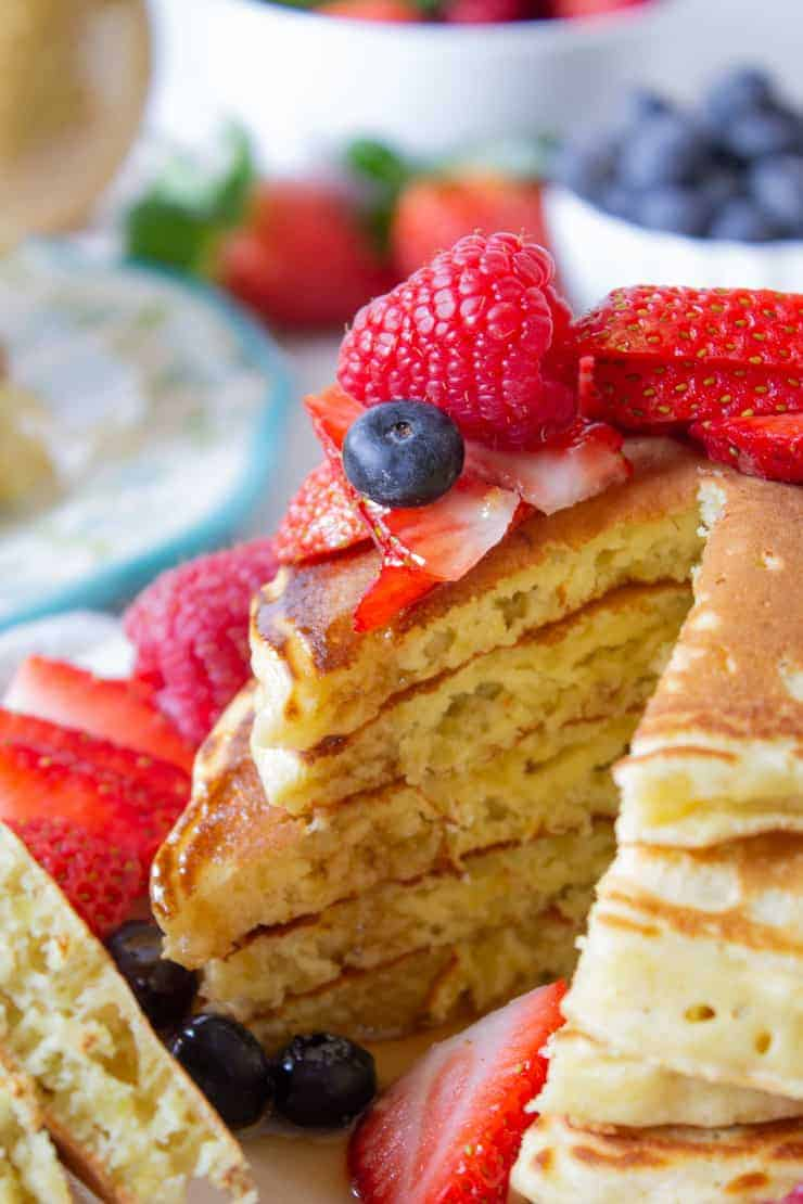 A stack of quinoa pancakes topped with fresh fruit