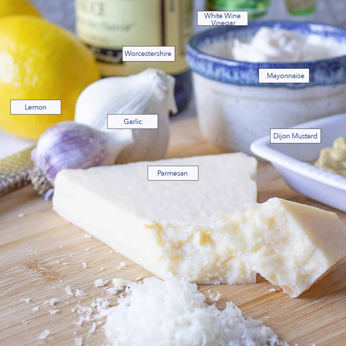 Grated parmesan cheese on a wooden cutting board with other ingredients behind the cheese.