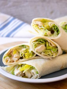 Chicken Caesar Wraps piled on a small blue and white plate.