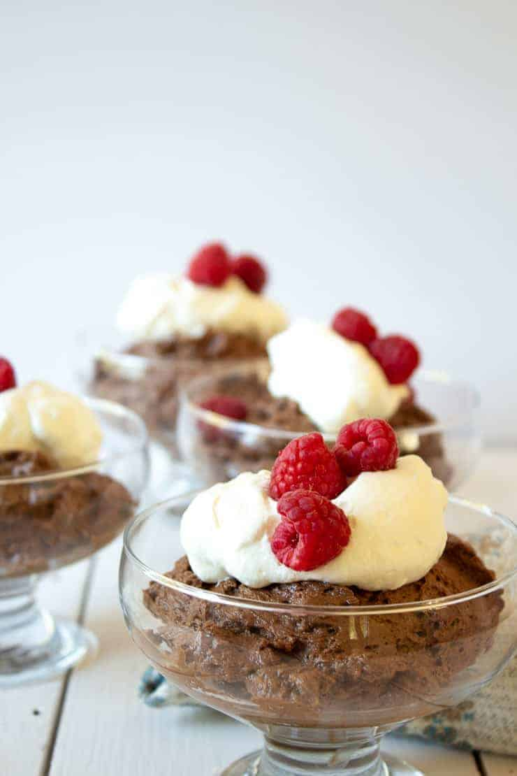 Homemade Chocolate Mousse topped with whipped cream and fresh raspberries.