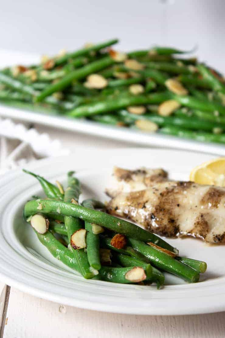 Green bean almondine on a white plate with a fillet of fish.