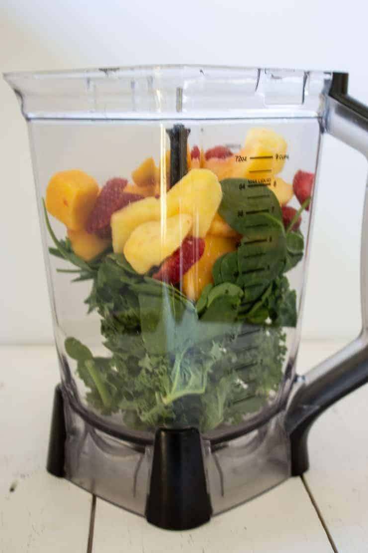 A blender full of frozen fruit, fresh spinach, and fresh kale for making a green smoothie.