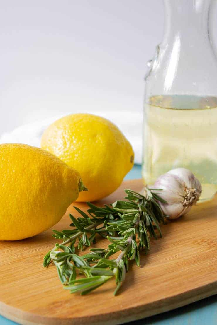 Fresh lemons, rosemary, garlic and white wine on a cutting board.