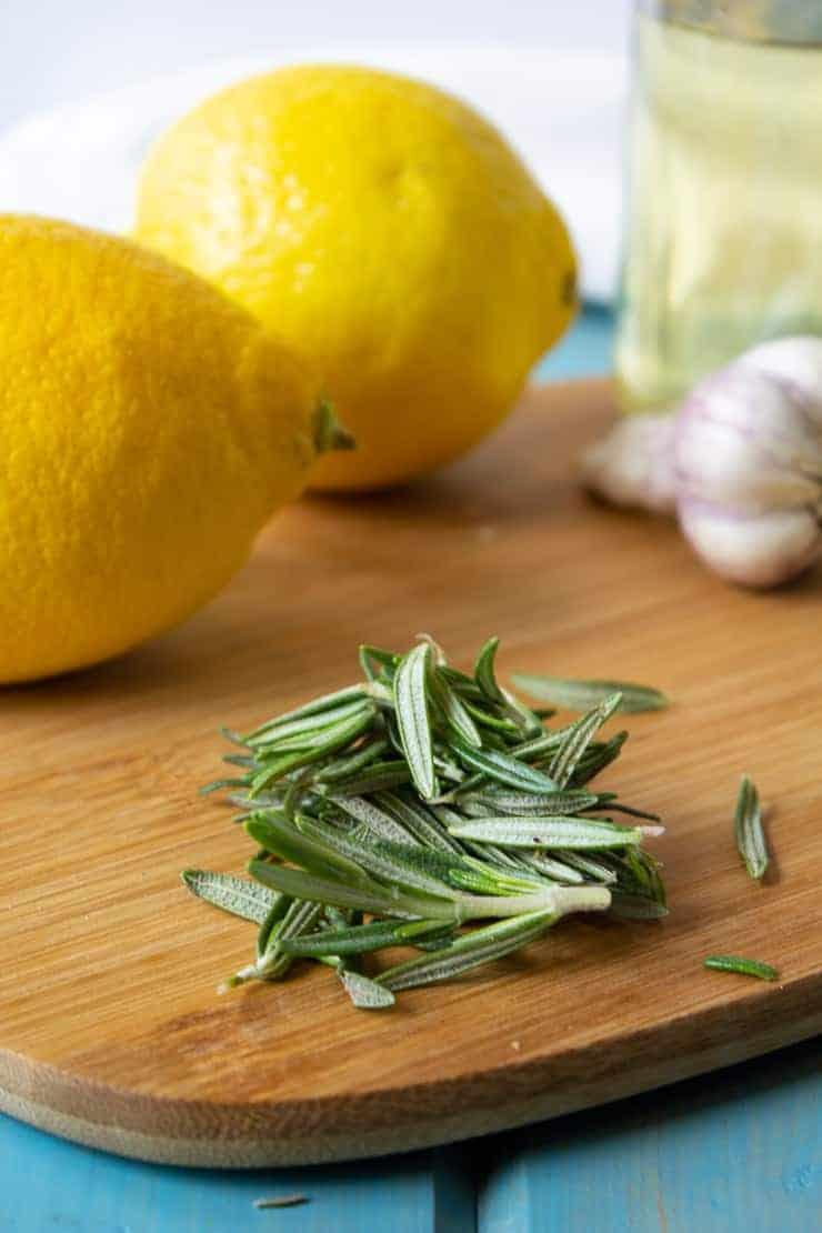 Fresh rosemary with fresh lemons and garlic on a cutting board.