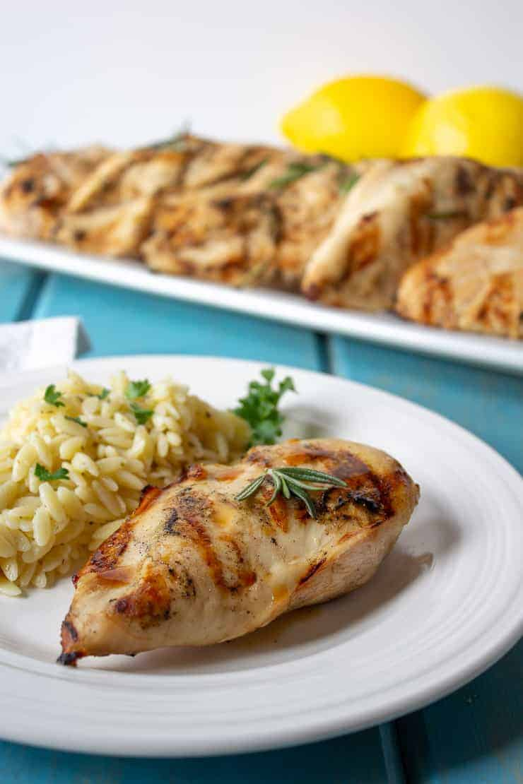 A grilled chicken breast on a white plate with orzo pasta next to the chicken.