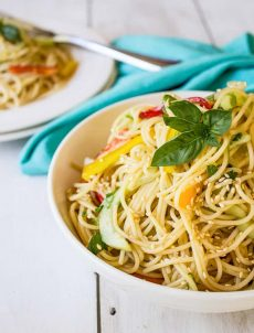 Thai Pasta Salad topped with a fresh sprig of basil