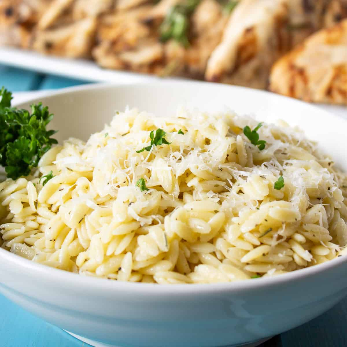 A bowl with orzo pasta topped with fresh green herbs.