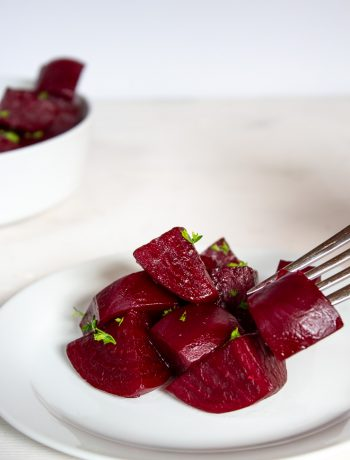 Gingered beets served on a small white plate with a fork