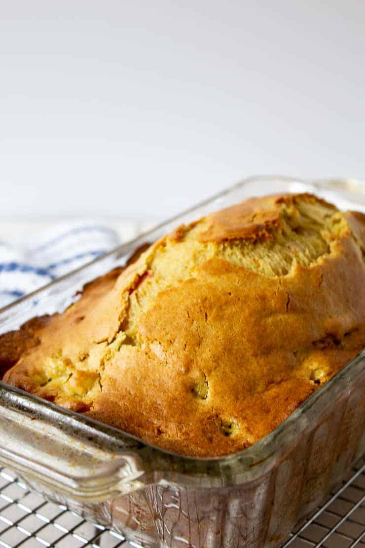 A loaf of rhubarb bread in a glass loaf pan.
