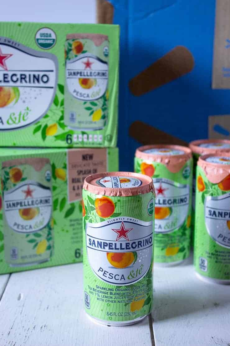 Sanpellegrino cans in front of a Walmart box.