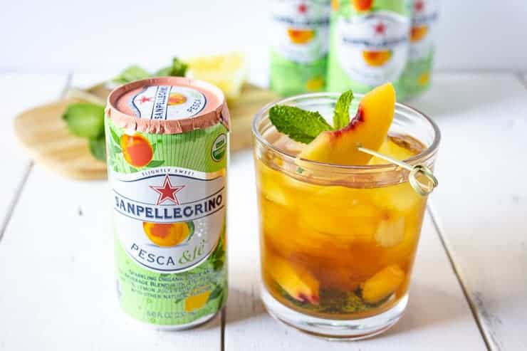 Sparkling Lemon Peach Tea Mocktail with a can of Sanpellegrino next to it.