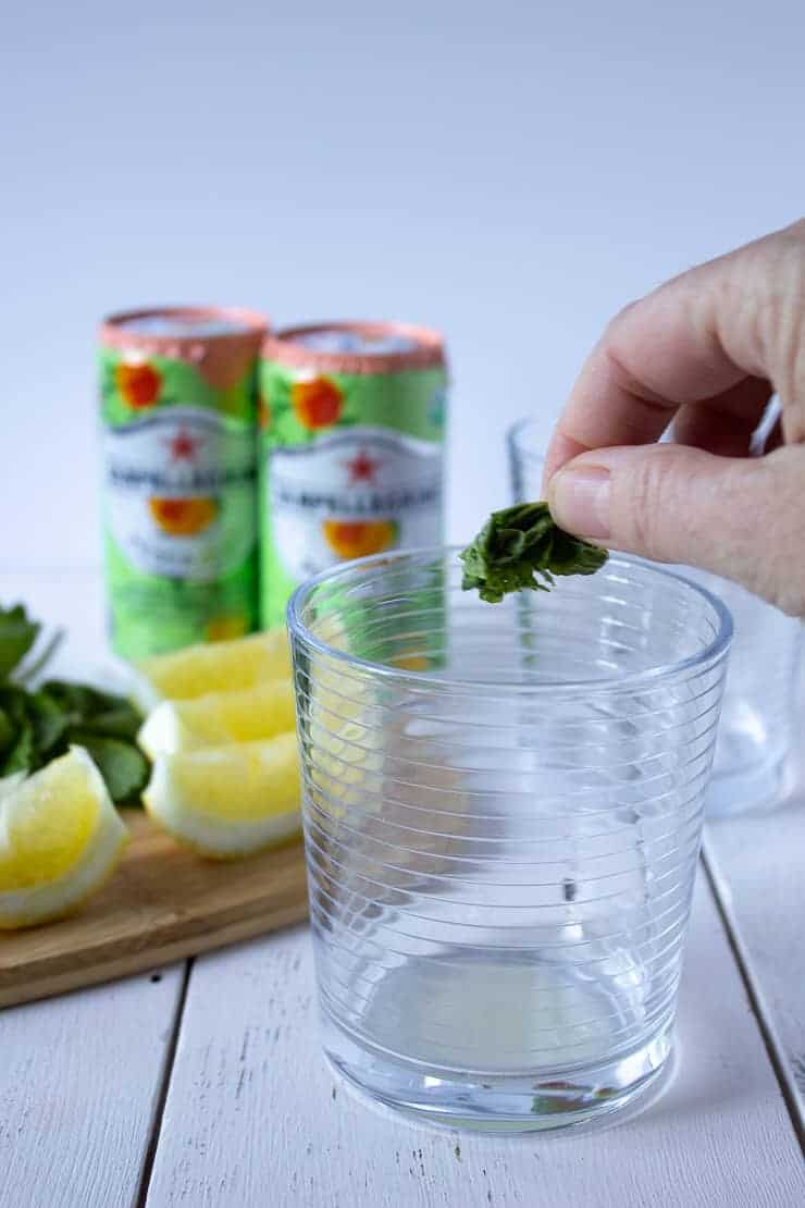 Adding smashed mint leaf into a glass.