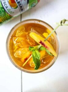 Sparkling Lemon Peach Tea with a fresh mint leave and a slice of peach for a garnish.