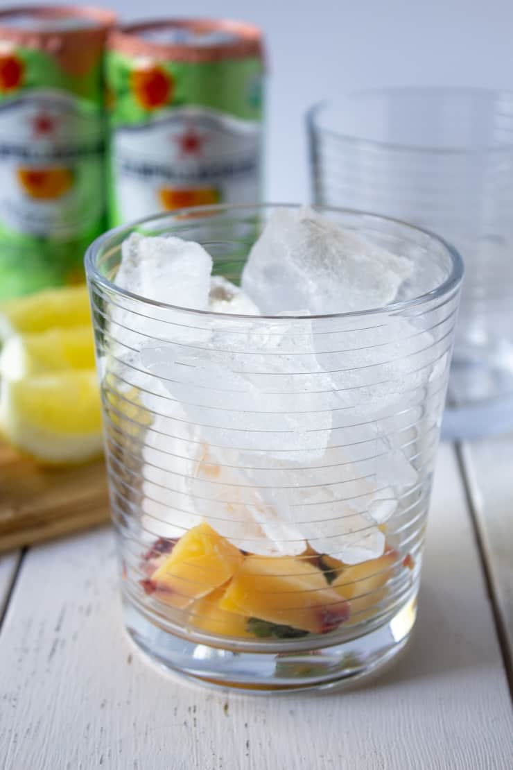 A glass filled with ice, chopped peaches, mint and lemon juice.