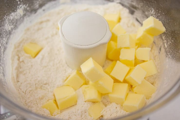 A food processor with a flour mixture and small cubes of butter.
