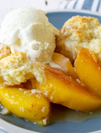 Peach slices topped with a cobbler topping and a scoop of vanilla ice cream.