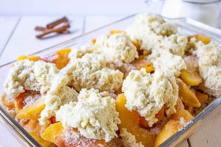Peach slices topped with mounds of biscuit dough.