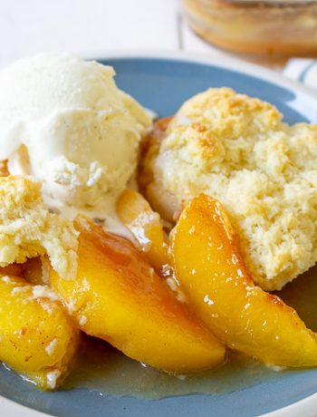 Peaches with a cobbler topping and a scoop of ice cream on a blue plate.