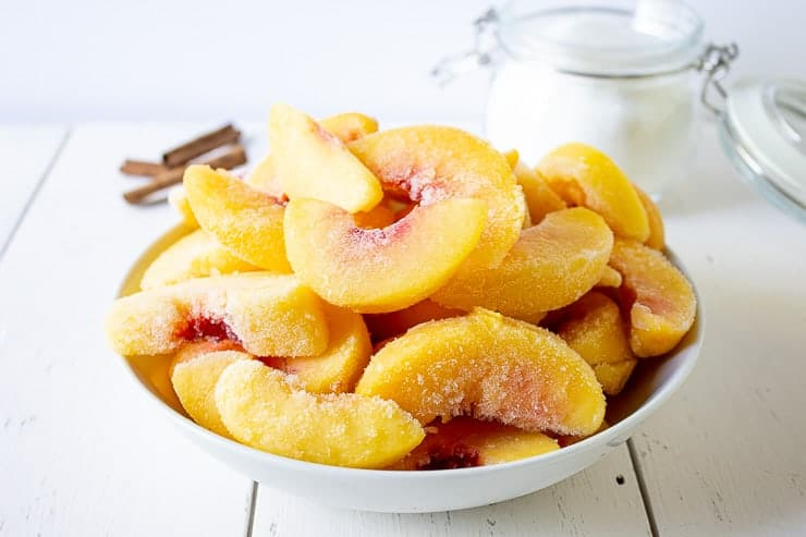 A white bowl filled with frozen peach slices.