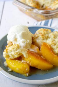 Peach slices topped with biscuits and vanilla ice cream.