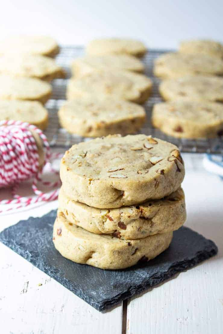 A stack of cookies with pecans on a black slate tile.