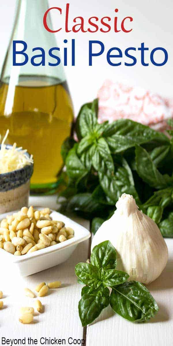 Fresh basil, garlic, pine nuts and olive oil arranged on a white board.