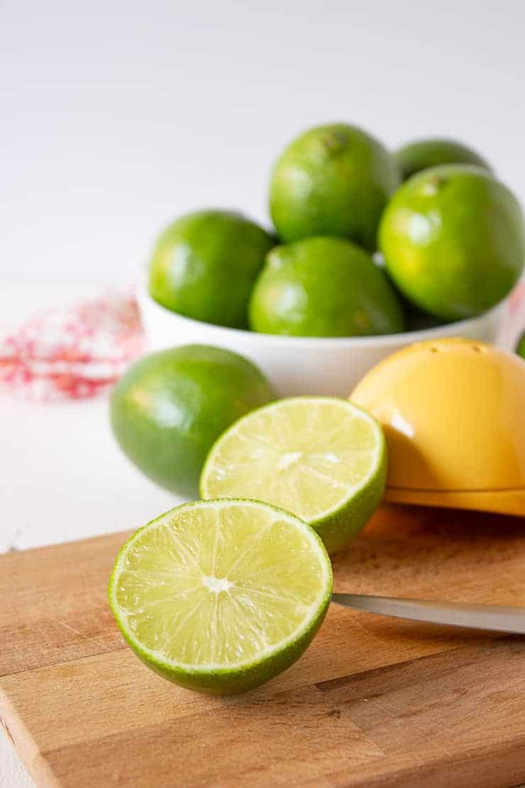 Fresh limes cut in half on a wooden cutting board.