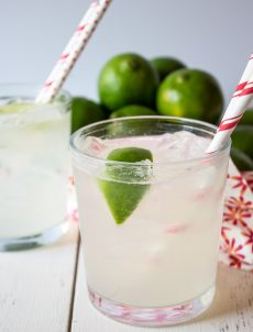A clear glass filled with ice and sparkling limeade.