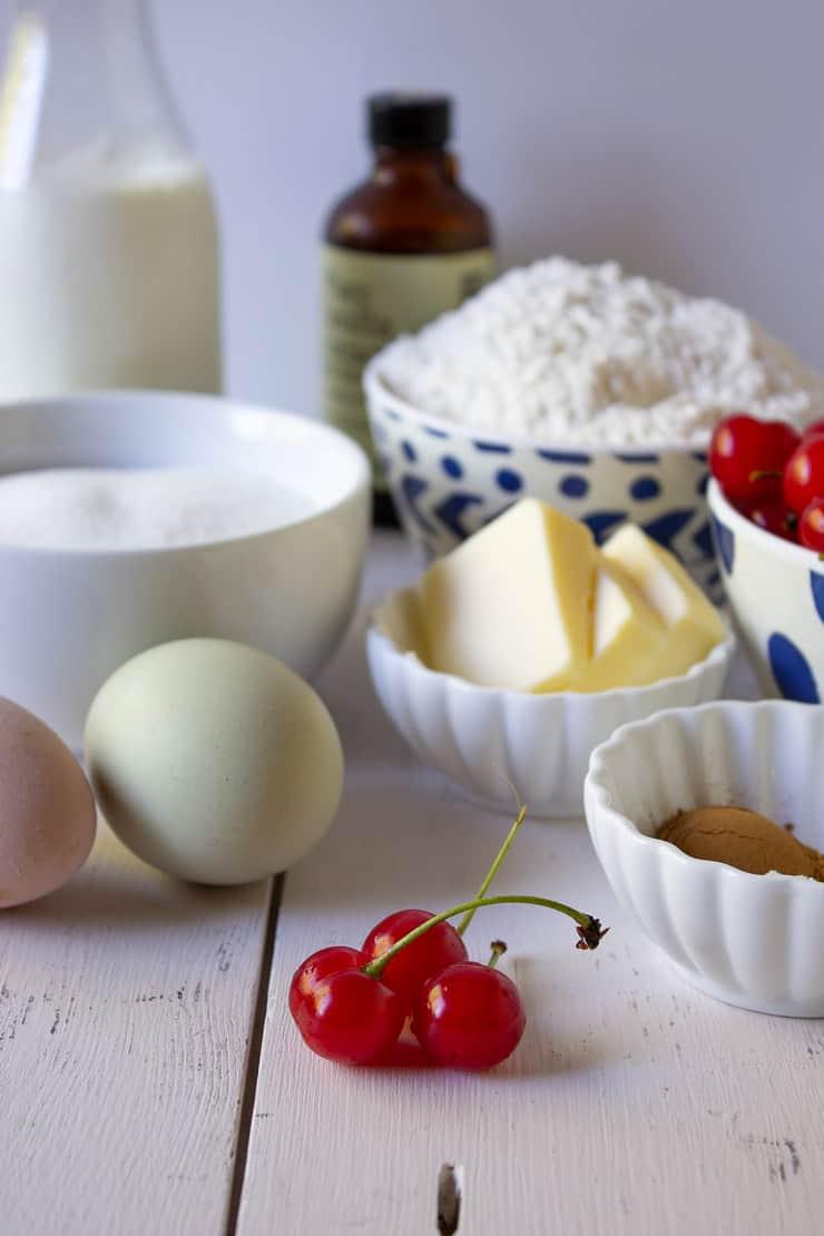 Fresh cherries, eggs, butter, flour and sugar on a white board.