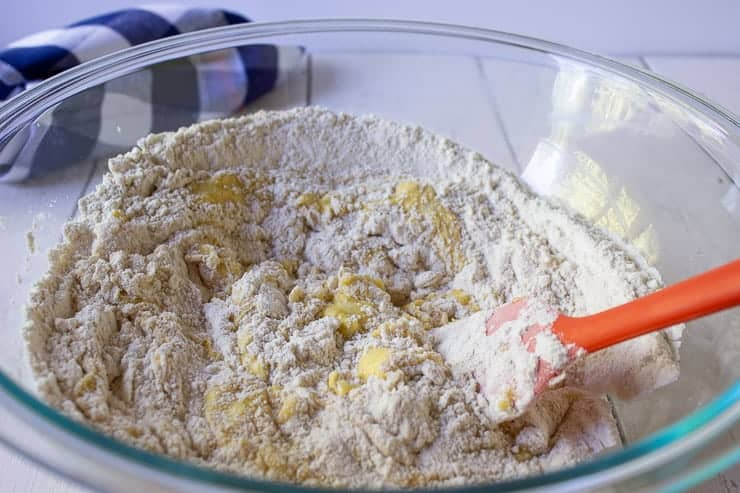 Cake batter being mixed together with an orange spatula.