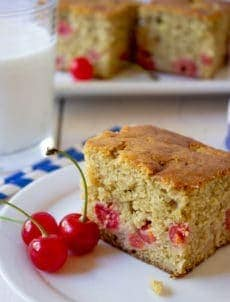 Slice of cake filled with cherries sitting on a white plate.