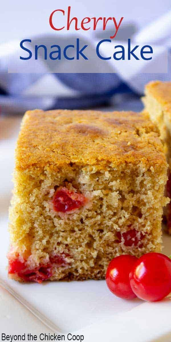 A slice of yellow cake with red cherries.