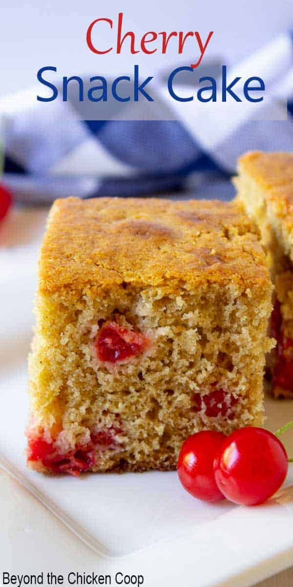 A square piece of yellow cake with red cherries in the cake.
