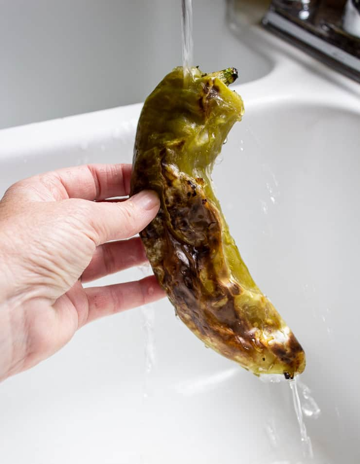 A roasted anaheim pepper held under running water in the sink.