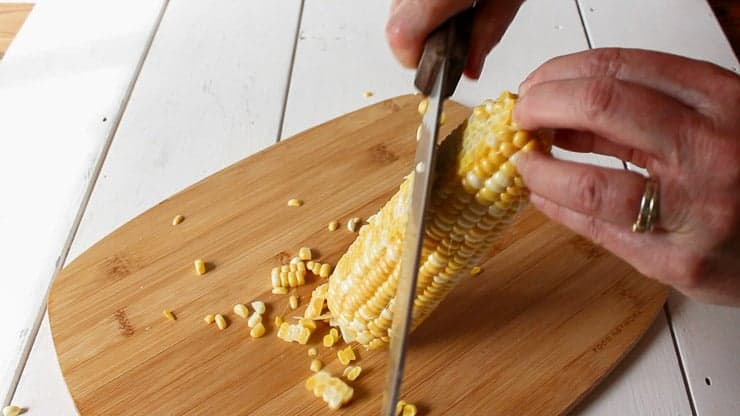 Cutting corn kernels off a cob.
