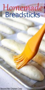 Long sticks of bread dough on a baking sheet with an orange brush adding butter to the tops.