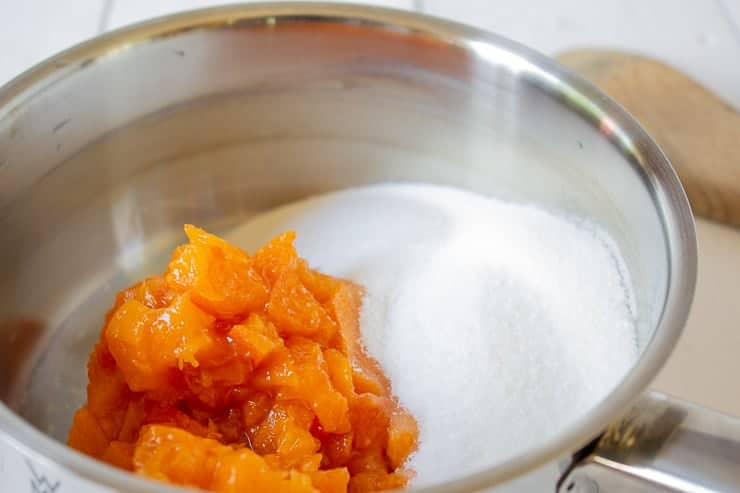 Chopped apricots and sugar in a sauce pot.