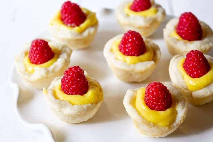 Lemon Curd Tartlets on a white serving dish.