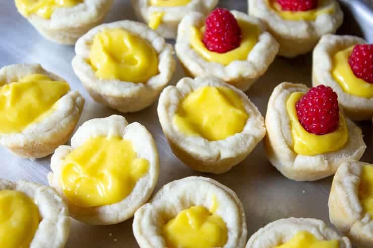Fresh raspberries added to lemon curd tarts.