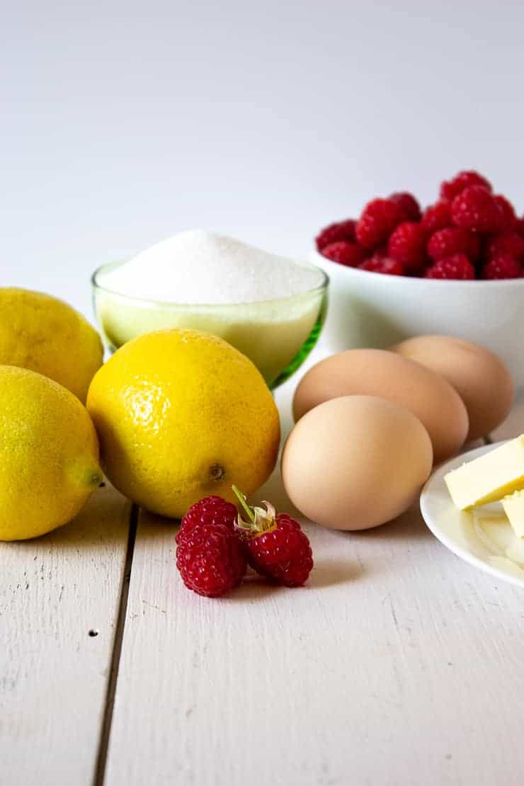 Fresh raspberries with lemons, eggs, sugar and butter all displayed on a white board.