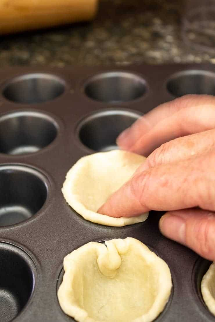 Placing pie crust dough into a mini muffin tin.