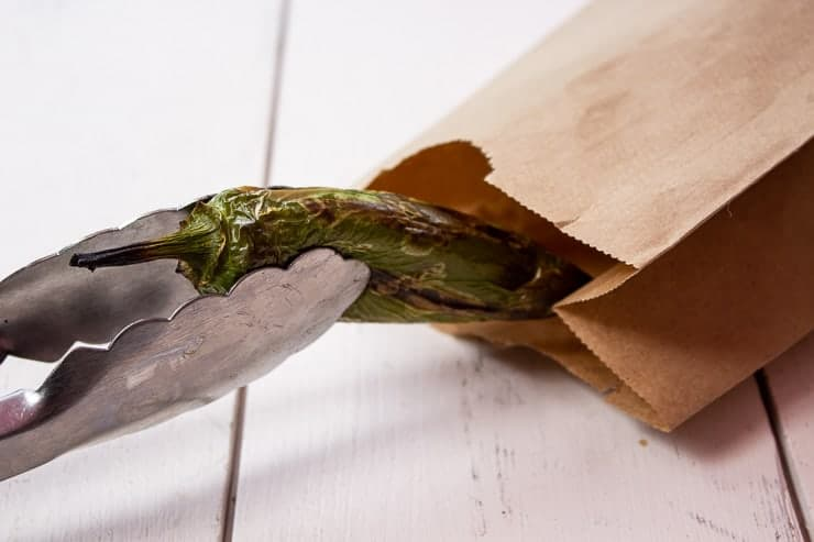 Roasted jalapeno pepper being placed into a paper bag.