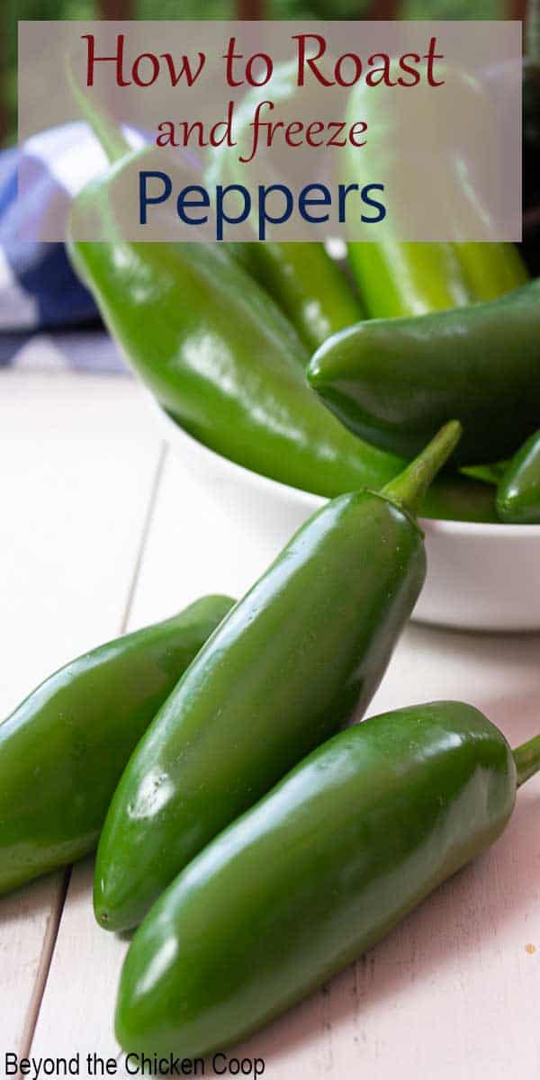 Fresh jalapenos sitting on a white board in front of a bowl of peppers.